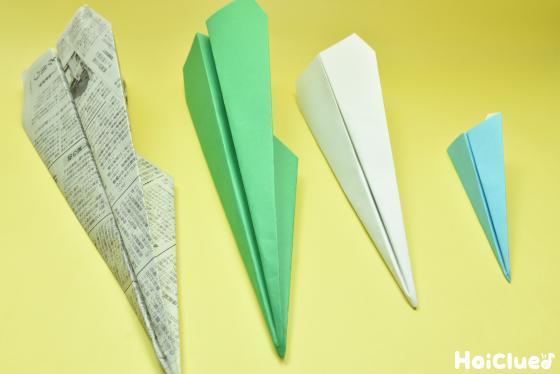 新聞紙・色画用紙・折り紙で折られた紙飛行機の写真
