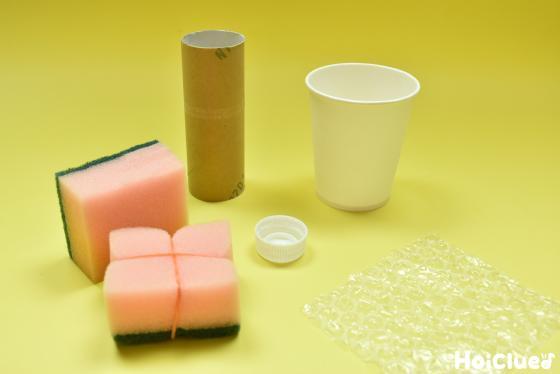 正方形に切り輪ゴムをかけたスポンジ、紙コップ、ペットボトルキャップ、トイレットペーパーの芯、プチプチの写真