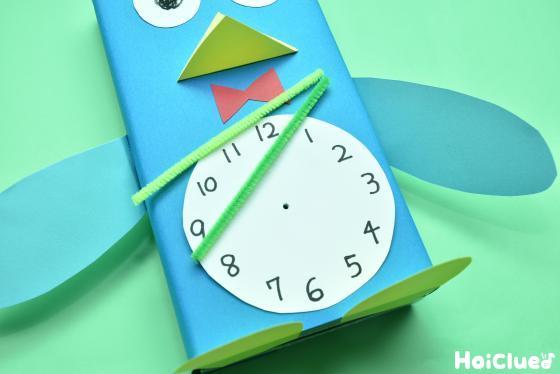 時計の真ん中に穴を開けモールを差し込む様子