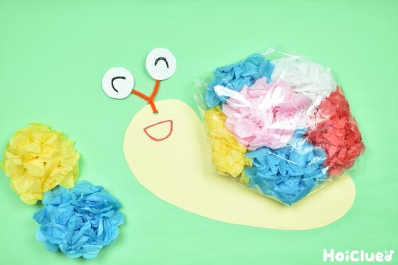 お花の形にした花紙を詰めたポリ袋のかたつむりの写真