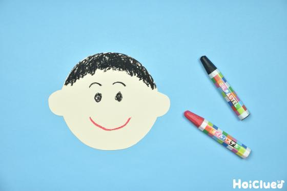 クレヨンで顔を描いた色画用紙