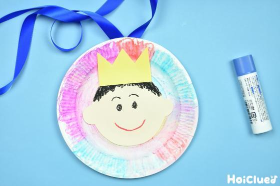紙皿に顔と王冠を貼りリボンをつけた写真