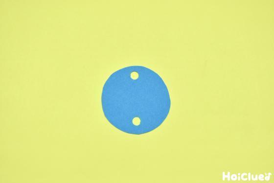 丸い色画用紙に2つの丸い穴を開けた写真