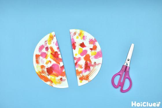 2つに切った紙皿とハサミの写真