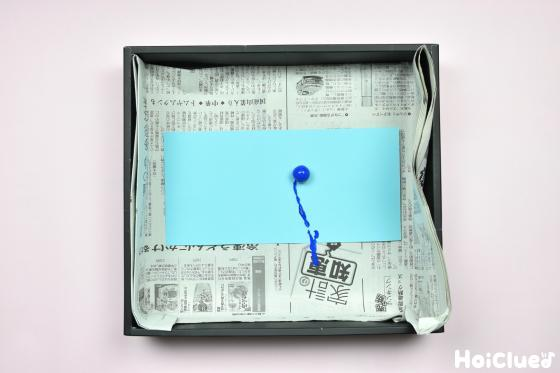 空き箱に水色の色画用紙を敷いたところに絵の具をつけたビー玉を投入した写真