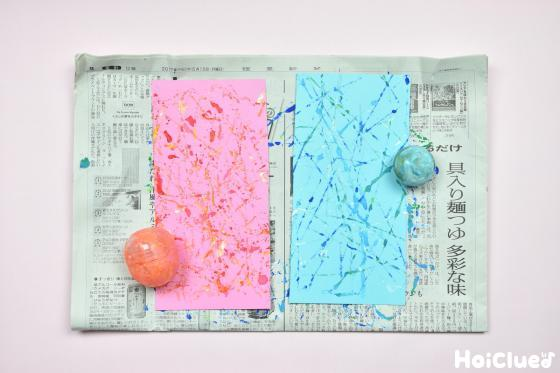 色付けされた2色の色画用紙とガチャガチャの容器の写真