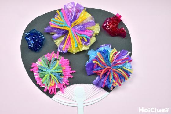 カラフルな花火と丸めたカラーセロファンで飾り付けたうちわ
