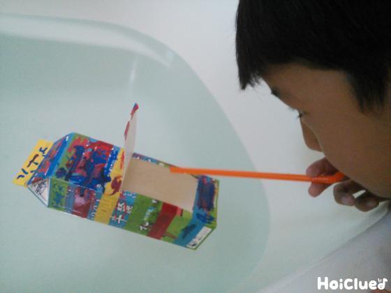 水に浮かべた船をストローで吹いて遊ぶ子どもの様子