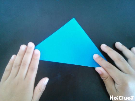 折り紙を三角に半分に折っている様子