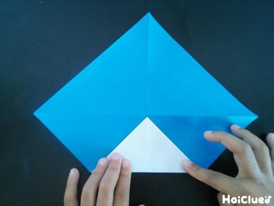 開いた折り紙の中心に角を折り上げている様子