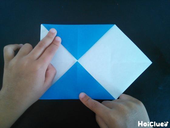 裏返した折り紙の別の角2つを折り上げている様子
