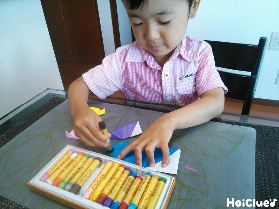 出来上がった折り紙の魚に顔や模樣を描く子どもの様子