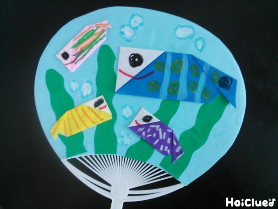 うちわに折り紙の魚をのりで貼った写真