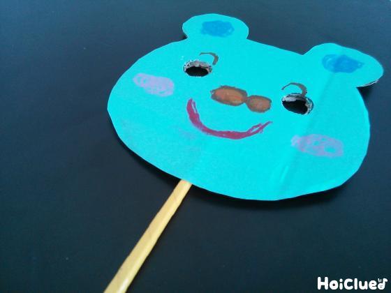 顔の下部分から割り箸を挟んだダンボール