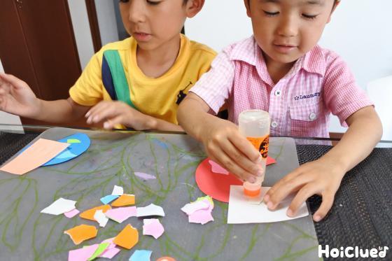折り紙にノリを付けて色画用紙に貼り付けている写真