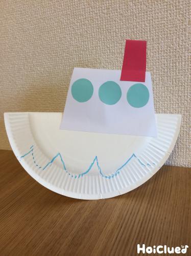 窓や煙突のある紙皿の船の写真