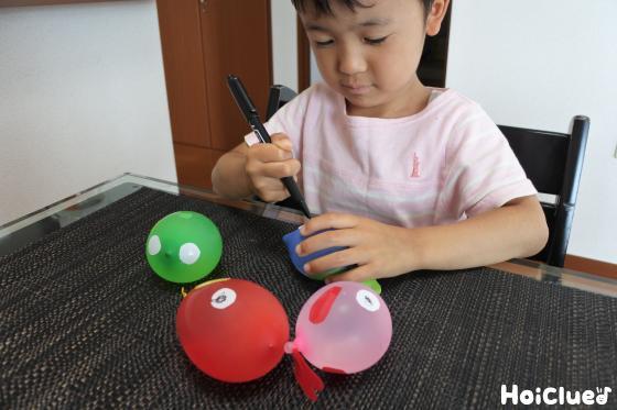 油性ペンで目を描く子どもの様子