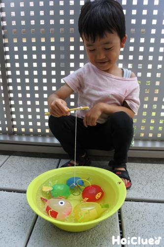 洗面器に浮かべた魚を釣って遊ぶ子どもの様子