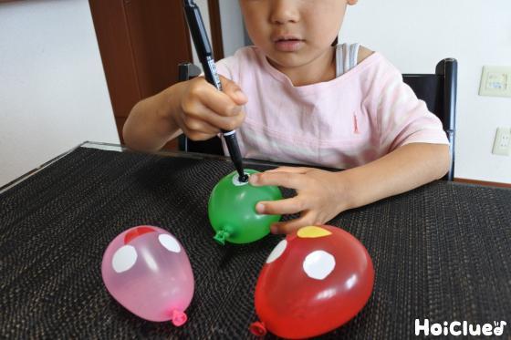 水風船に油性ペンで黒目や模樣を描く子どもの様子