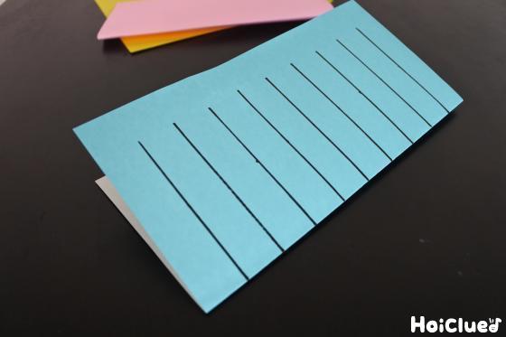 半分に折り長方形にした折り紙に等間隔で縦線を引いた写真