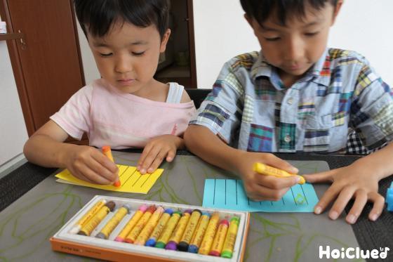 折り紙に貝がらの絵を描く子どもたちの様子