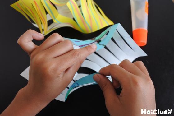 開いた折り紙の、対角線上の角と角をのりで貼る様子
