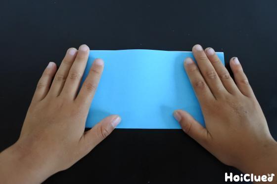 半分に四角く折った青い折り紙