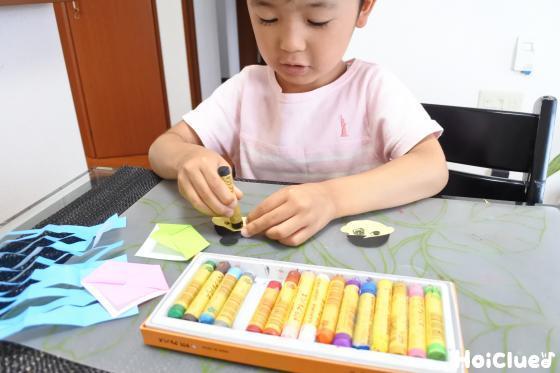 色画用紙で作った顔に目などを描く子どもの様子