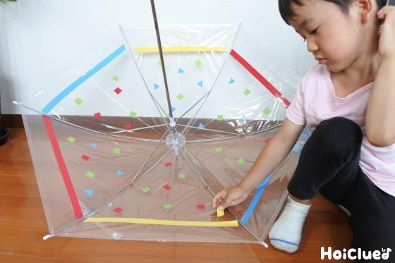 ビニール傘の内側をビニールテープで飾り付ける子どもの様子