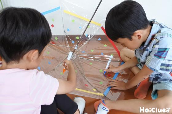 ビニール傘の内側に油性ペンで絵を描く子どもたち