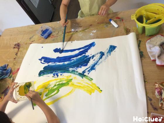 黄色と青の絵の具を広げる子どもたちの様子