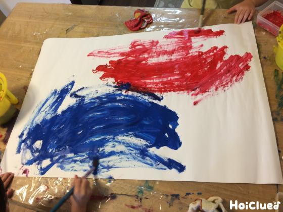 赤と青の絵の具を広げる子どもたちの様子