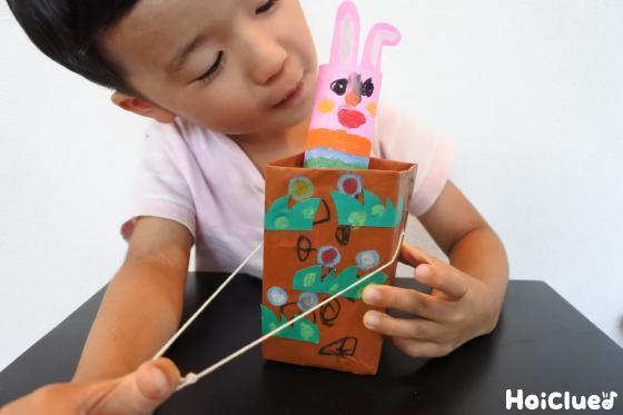 タコ糸を引っ張り牛乳パックから飛び出すうさぎのおもちゃで遊ぶ子どもの様子