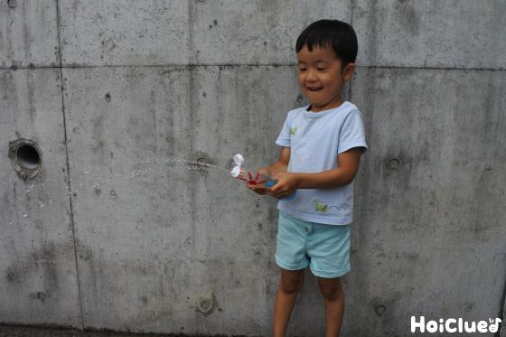 ケチャップ容器を押して水を噴射する子ども