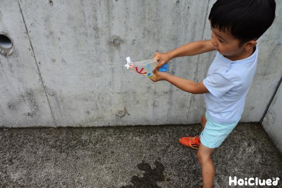 ケチャップ容器を強く押して水を噴射する子ども