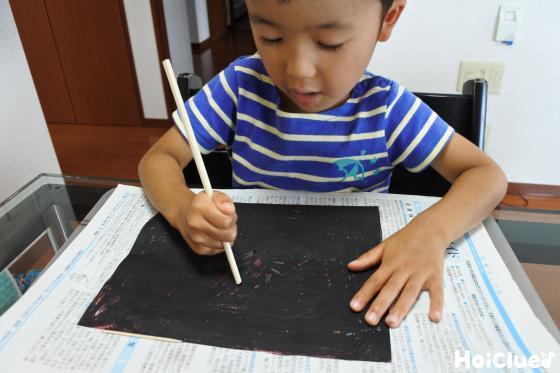 黒い包装紙を割り箸でこする様子