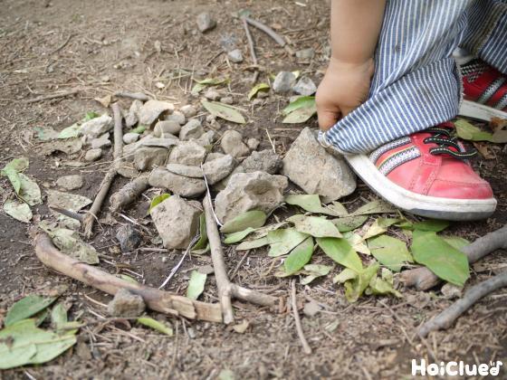 木の枝や石と子どもの足
