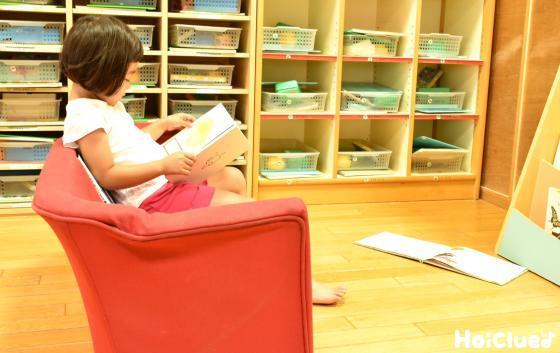 椅子に座って絵本を読む女の子