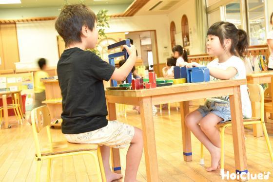 テーブルに向かい合って座り積み木を楽しむ子どもの様子