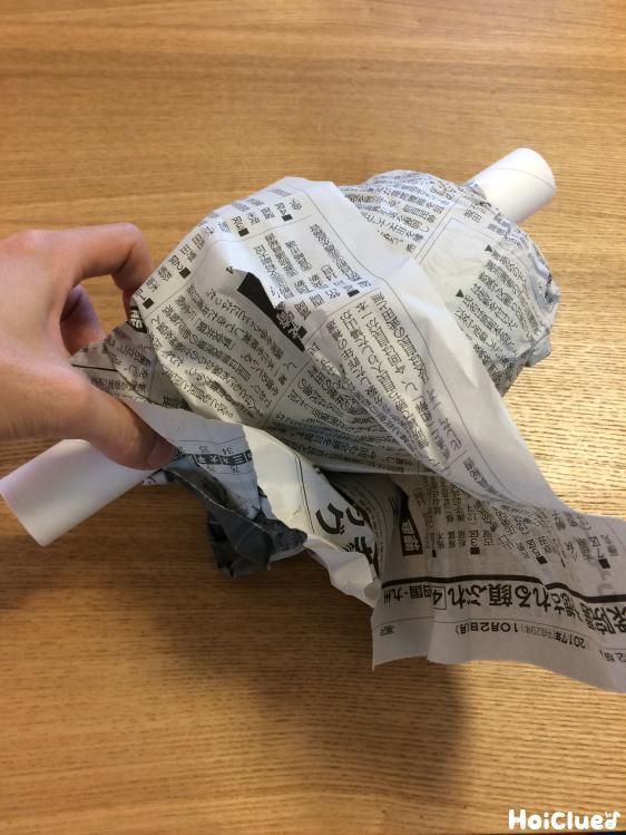 ラップの芯に新聞紙を巻く様子