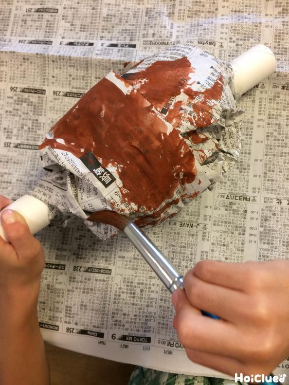 新聞紙に色を塗る様子