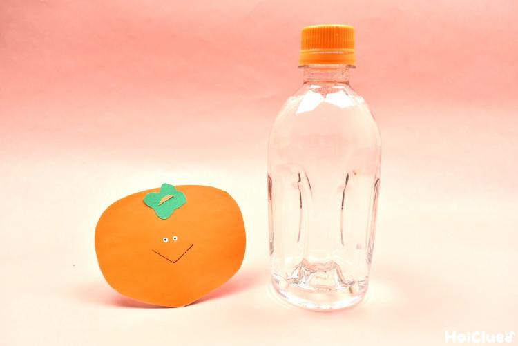 画用紙の柿と水の入ったペットボトルの写真