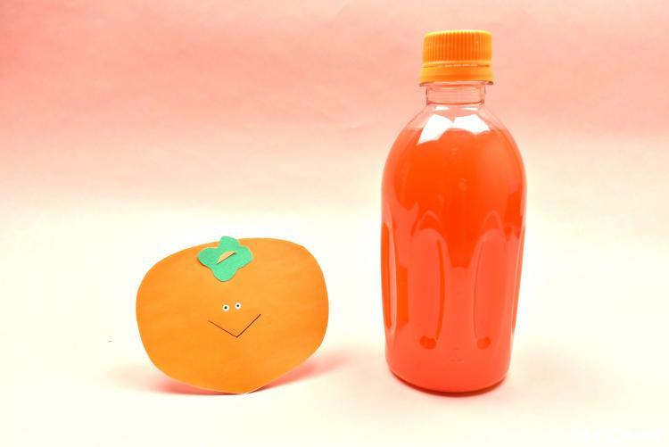 画用紙の柿とオレンジ色の水が入ったペットボトル