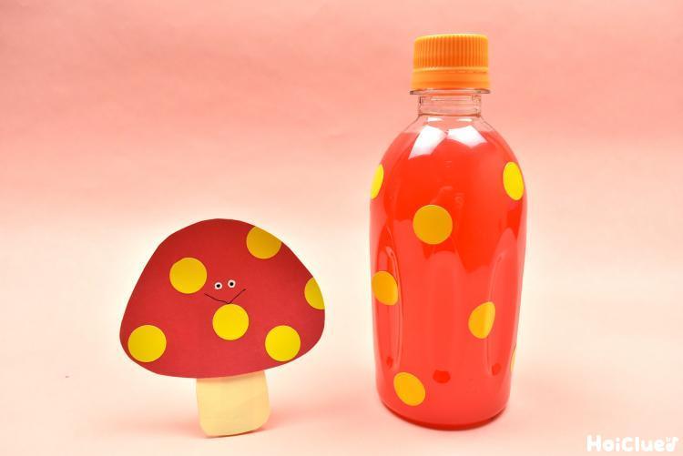 画用紙のきのこと丸シールを貼りオレンジ色の水の入ったペットボトル