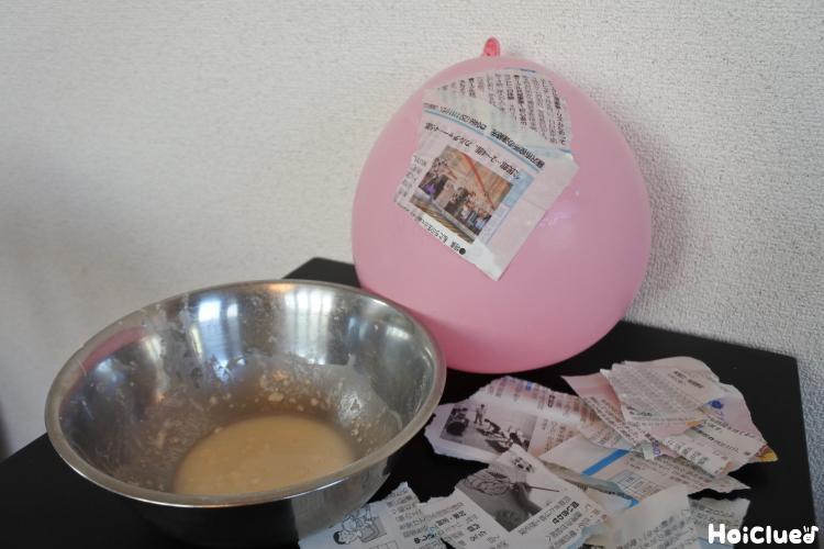 新聞紙を風船に貼り付けている写真