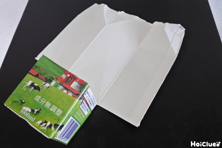 牛乳パックの側面を下の部分を残して切り開いた写真