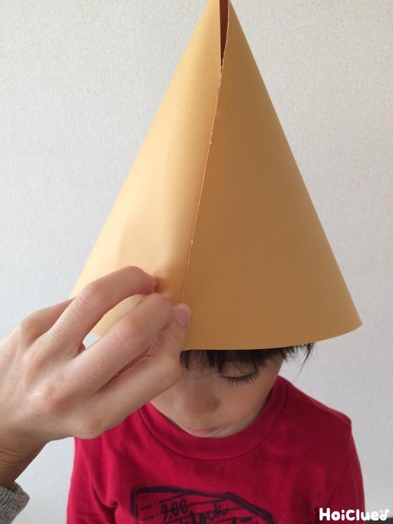 子どもの頭に合わせて帽子のサイズを決める様子