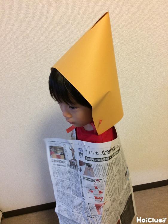 帽子と蓑を着る子どもの写真