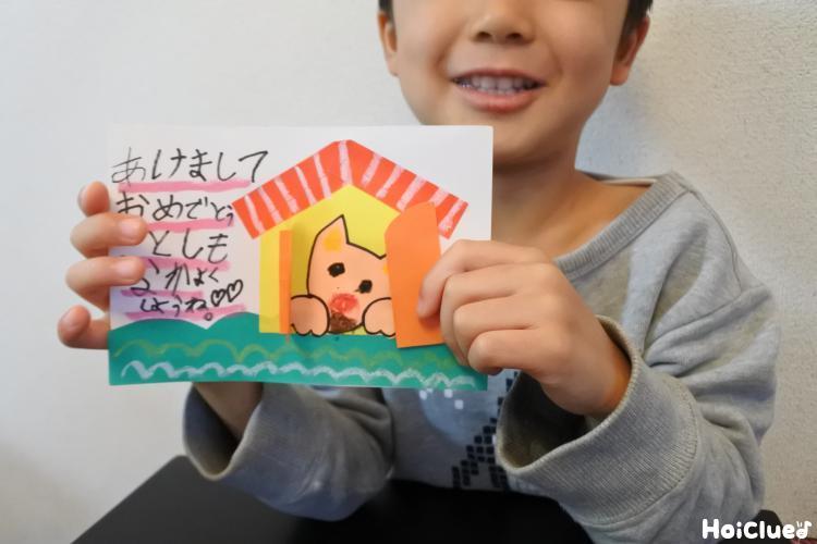 完成した葉書を手に持つ子どもの写真