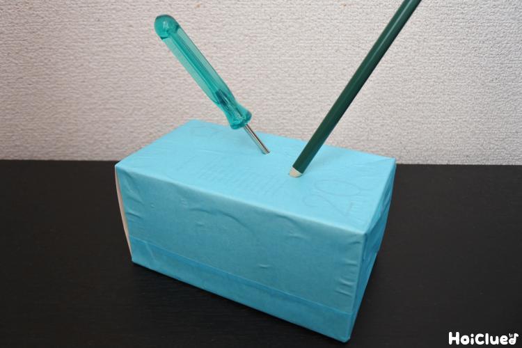 画用紙を貼った箱に穴を開ける様子